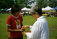 Montreal (Qc) CANADA , June 6, 2006<br /> <br /> Filippina girl getting   the communion during  the filippino national holliday celebrations,<br />  in a Montreal park.