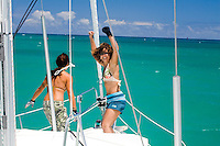 Young women on the bow of a sailboat in clear water, leaving Kaneohe Bay, Oahu, Hawaii