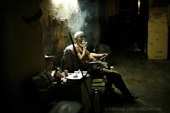 An elderly man smokes a cigar inside a garage in Old Havana, Cuba on 12 October 2008.
