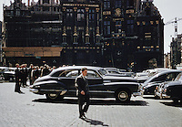 People walking on street with cars by buildings