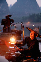 Detail image of a Li River Cormorant fishermen on a bamboo raft lighting a lantern at dusk. Guilin Guangxi, China.
