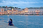 A couple sits on Molo Audace pier at sunset, looking at Piazza Unita d'Italia in the background in Trieste, Italy