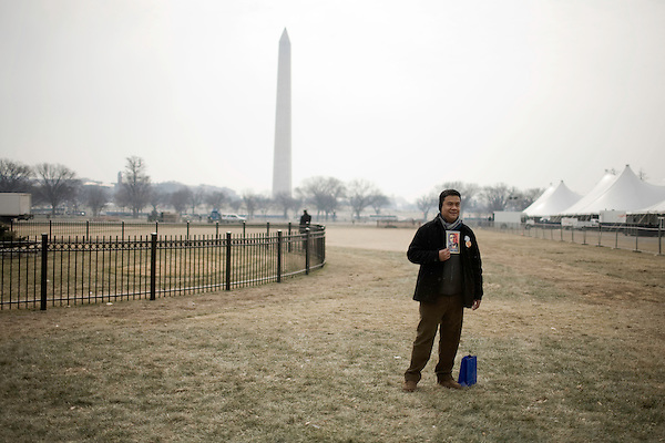 January 19, 2009. Washington, DC..Thousands of people congregated on the National Mall on the day before the inauguration of Barack Obama, the 44th president of the United States.. A man posed with a sticker of the new president near the Washington Monument.