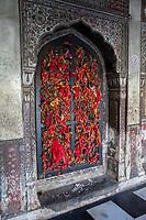India, Dehradun.  Visitors tie bits of red cloth to the window latticework as a symbol of prayers offered at the Sikh Temple Durbar Shri Guru Ram Rai Ji Maharaj, built in 1707.