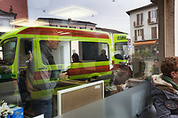 Switzerland. Canton Ticino. Stabio. Day scene for a medical emergency intervention. Ambulance's reflection in a cafe's window. Customers enjoy their morning coffee while others are outside smoking a cigarette. A senior man suffering from severe pains in the hip has to be brought to hospital by an ambulance from theCroce Verde Lugano. TheCroce Verde Lugano is a private organization which ensure health safety by addressing different emergencies services and rescue services. 27.01.2018 © 2018 Didier Ruef