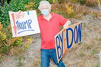 """A man holds a sign reading """"Dump Trump"""" and """"ByeDon"""" as Donald Trump, Jr., son of president Donald Trump and a rising Republican political star, leaves after speaking at an outdoor campaign rally at The Lobster Trap in North Conway, New Hampshire, on Thu., Sept. 24, 2020."""