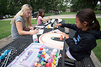 Ellie Trainor of Fayetteville (left) helps Abby Stewart ,12, (right) and Anna Stewart, 9, with an art project Monday July 19, 2021 at Wilson Park in Fayetteville. Trainor is the girl's nanny for the summer. Visit nwaonline.com/21000720Daily/ and nwadg.com/photo. (NWA Democrat-Gazette/J.T. Wampler)