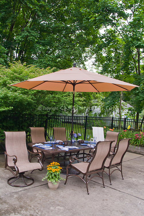 Patio, table, chairs, furniture, set for dining, fence, umbrella, iron fence, raised beds of daylilies