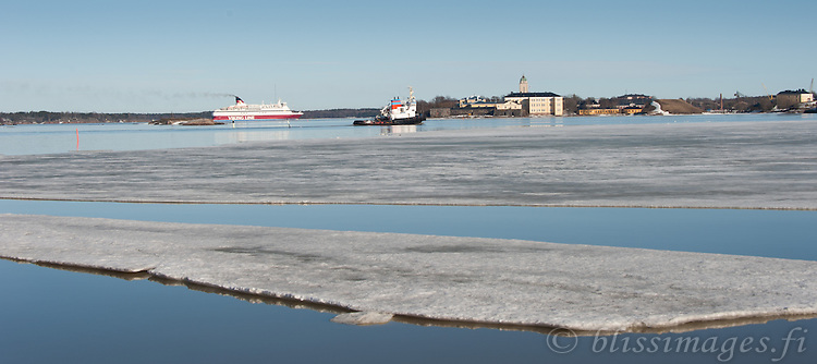 Viking Line and tugbost Atlas steam towards Suomenlinna Lighthouse Fortress in winter at Helsinki, Finland.