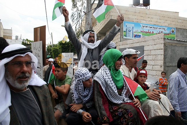 """Palestinian protestors ride a donkey during a protest against Israel's controversial separation barrier and to mark the 63th anniversary of """"Nakba"""" (catastrophe) on May 13, 2011in the West Bank village of Bilin. Nakba means """"catastrophe"""" in reference to the birth of the state of Israel 63 years ago in British-mandate Palestine, which led to the displacement of hundreds of thousands of Palestinians who either fled or were driven out of their homes during the 1948 war over Israel's creation. Photo by Issam Rimawi"""
