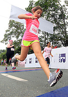 A runner crosses the finish line during the 32nd annual Charlottesville Women's Four Miler race Saturday in Charlottesville, VA. Photo/The Daily Progress/Andrew Shurtleff