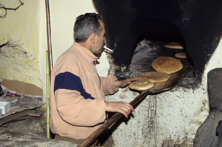 Meknes, Morocco - A Baker Removes Baked Bread from his Oven.