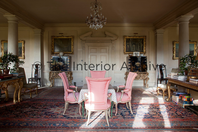 The furniture in the reception room is arranged in a symmetrical fashion on either side of a pedimented doorway
