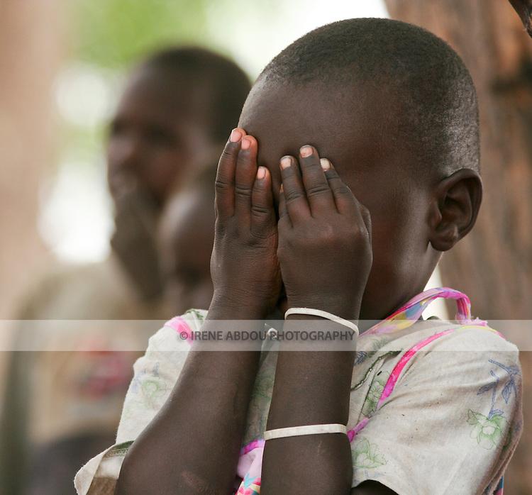A girl in Rumbek, South Sudan plays peek-a-boo.
