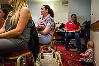 A mother breastfeeding her baby while listening to a speaker  at a conference.<br /> <br /> West Midlands, England, UK<br /> 07/06/2014<br /> <br /> © Paul Carter / wdiip.co.uk