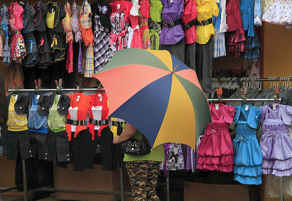 Woman behind umbrella shopping at outdoor market in Denver, Colorado. .  John offers private photo tours in Denver, Boulder and throughout Colorado. Year-round Colorado photo tours.