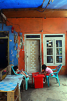 Two children sit outside a colorful house in a slum community in central Jakarta.<br />