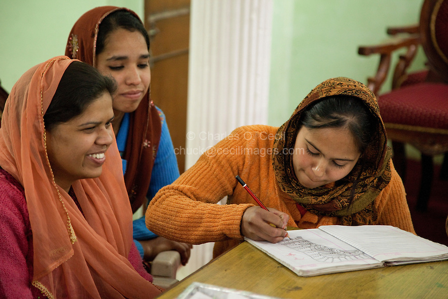 Dehradun, India.  Young Muslim Indian Woman Drawing a Henna Design in her Notebook.