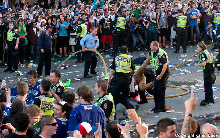 A rioters is hauled away by emergency officers after cars were burned on the downtown streets of Vancouver,BC after the Canucks were defeated by the Boston Bruins in the Stanly Cup on June 15, 2011. (photo copyright Karen Ducey)
