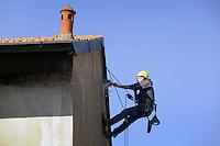 - Milano, operaio edile esegue lavori di manutenzione sul tetto di un condominio<br /> <br /> - Milan, construction worker performs maintenance work on the roof of an apartment building
