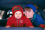 A mother and daughter smiling while looking out the backdoor of a vehicle, Rocky Mountains, CO