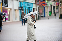 Friday 14 February 2014<br /> Pictured:A Woman Walks along under the cover of her umbrella<br /> Re: Rain and gale force winds are again due to batter the UK