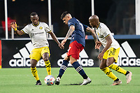 FOXBOROUGH, MA - MAY 16: Gustavo Bou #7 of New England Revolution passes under pressure from Harrison Afful #25 Columbus SC and Darlington Nagbe #6 Columbus SC during a game between Columbus SC and New England Revolution at Gillette Stadium on May 16, 2021 in Foxborough, Massachusetts.