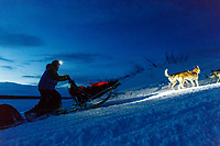 Linwood Fiedler and team run up the bank of the Yukon River and into the Kaltag checkpoint as dawn breaks on Sunday March 10th during the 2019 Iditarod Trail Sled Dog Race.<br /> <br /> Photo by Jeff Schultz/  (C) 2019  ALL RIGHTS RESERVED