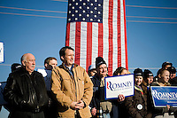 """Former governor of Minnesota and Republican presidential candidate Tim Pawlenty (brown jacket) stands with Romney supporters as Republican presidential candidate Mitt Romney, former governor of Massachusetts, speaks during a rally in Manchester, New Hampshire, on Sat. Dec. 3, 2011. The rally was called, """"Earn It with Mitt,"""" and was designed to bolster local efforts to help Romney """"earn"""" voters' support for the upcoming Republican primary."""