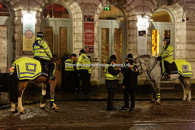 Pictured: Police officers speak to two young men. Sunday 31 December 2017 and 01 January 2018<br /> Re: New Year revellers in Wind Street, Swansea, Wales, UK