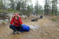 Photo story of Philmont Scout Ranch in Cimarron, New Mexico, taken during a Boy Scout Troop backpack trip in the summer of 2013. Photo is part of a comprehensive picture package which shows in-depth photography of a BSA Ventures crew on a trek.  In this photo a BSA Venture Crew member assumes the lightening position on his backpack, as multiple lightening strikes surrounded the crew as the made their  way through heavy driving rains in the backcountry at Philmont Scout Ranch.   <br /> <br /> The  Photo by travel photograph: PatrickschneiderPhoto.com