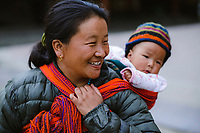 Candid portrait of mother carrying baby in a back-sling in Thimpu, Bhutan