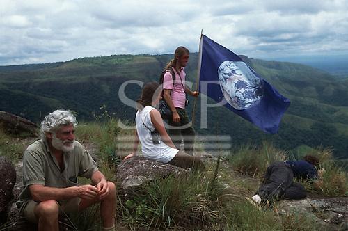 Chapada dos Guimaraes, Mato Grosso, Brazil. Ed Posey, Liz Hosken and Mario Friedlander on Mount São Geronimo with the Gaia flag; 1990.
