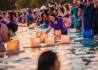 On Memorial Day, an Asian woman places a lantern into the water during the 15th Annual Lantern Floating Ceremony at Ala Moana Beach Park, Honolulu, O'ahu.