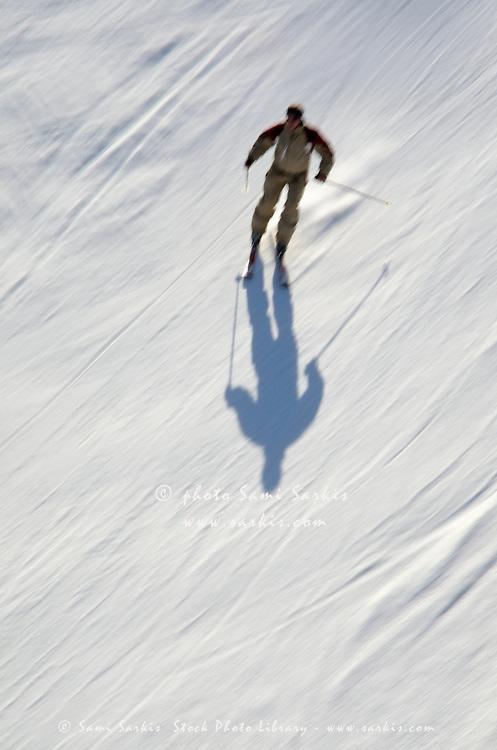 Skier speeding on snow (blurred motion), French Alps, France