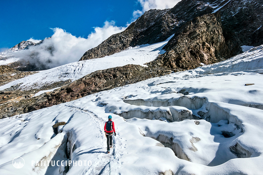 Descending a glacier on the normal route of the 4000 meter Weissmies, Switzerland, a climber walks alongside crevasses.