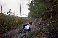 Manny Babbitt, 12, looks at foliage while he and other sixth grade students from Roger Williams Middle School in Providence, Rhode Island, walk along a trail at the Powder Mill Ledges Wildlife Refuge in Smithfield, Rhode Island, on Oct. 20, 2011. The students are part of the EcoExplorer program run by the Providence After School Alliance, which helps to kids in learning environments outside of school time.  <br /> The students make a weekly visit to the refuge, operated by the Rhode Island Audubon Society, to learn about nature and ecology.<br /> <br /> <br /> M. Scott Brauer for Education Week