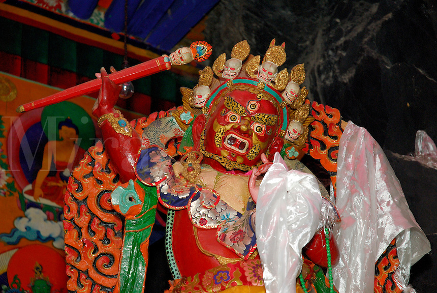 Red protector deity Tamdrin with tiara of skulls, wearing tiger skin, draped with white silk prayer scarves, in the cave temple at Palha Lupuk, Lhasa, Tibet, China.