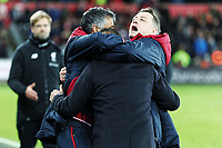 Swansea manager Carlos Carvalhal (C) is embraced by colleagues coach Joao Mario and Tony Roberts during the Premier League match between Swansea City and Liverpool at The Liberty Stadium, Swansea, Wales, UK. Monday 23 January 2018