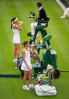 24-06-13, England, London,  AELTC, Wimbledon, Tennis, Wimbledon 2013, Day one, Ana Ivanovic (SRB) and Virginie Rozzano (FRA)( foreground) drinking during changeover<br /> <br /> <br /> <br /> Photo: Henk Koster