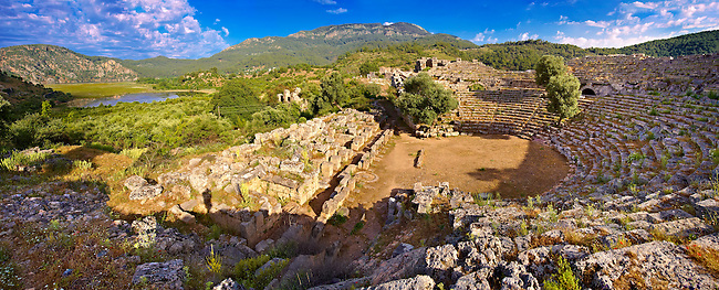 Kounos ampitheatre which could sit 5000 people. The theatre has hellanistic & Roman features. In the background is the silted up harbour. Kounos (Counos) Archaeological Site, Dalyan, Turkey