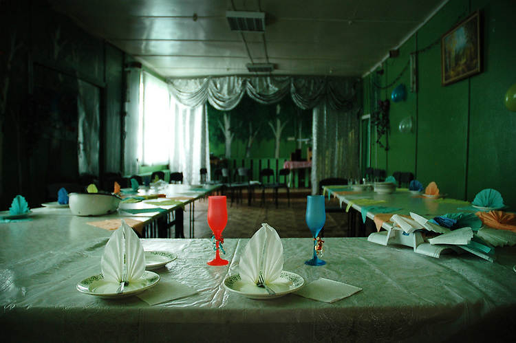 Tables are setting up for a wedding dinner in a village cafe. Most of young people leave their native villages right after finishing school to find a better life