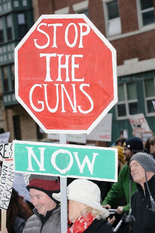 """People take part in the March For Our Lives protest, walking from Roxbury Crossing to Boston Common, in Boston, Massachusetts, USA, on Sat., March 24, 2018, in response to recent school gun violence. Here, a person holds a hand-made sign that looks like a stop sign and reads on one side, """"Stop the Madness / End Gun Violence,"""" and on the other, """"Stop the Guns / Now."""""""