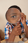6 year old's face enlarged in magnifying glass vertical