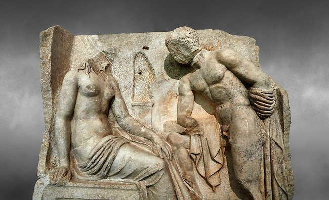 """Close up of a Roman Sebasteion relief  sculpture of Io and Argos Aphrodisias Museum, Aphrodisias, Turkey.  Against a grey background.<br /> <br /> A powerful hero is folding a sword gazing closely at a half naked and dishevelled young heroine who sits on a chest like stool. Between, on a pillar base stood a small, separately added statue of a goddess ( now missing). The scene follows a scheme used in the relief panels """"Io guarded by Argos"""". Io was one of Zeus's lovers, and Argos was a watchful giant sent to guard her by Hera, Zeus's wife."""