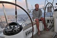 - leisure sailing boat in navigation on the Southern Mediterranean sea, sailor to the rudder wheel ....- barca a vela da diporto in navigazione nel mare Mediterraneo Meridionale, marinaio al timone