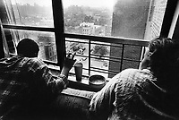 """USA. New York City. Spanish Harlem. Richie (L) and her mother Pat (R) are looking outside at 110 Street. Plastic glass and ashtray. The Puerto Rican family lives below the poverty line and receives public assistance (AFDC, Home Relief, Supplemental Security Income and Medicaid). The family resides in units managed by the New York City Housing Authority (NYCHA) which provides housing for low income residents. NYCHA administers rental apartments in facilities, popularly known as """"projects"""". Spanish Harlem, also known as El Barrio and East Harlem, is a low income neighborhood in Harlem area. Spanish Harlem is one of the largest predominantly Latino communities in New York City. 20.10.86 © 1986 Didier Ruef .."""
