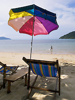 Thailand. Trat province. Sand beach near the village of Ban Bang Bao on Ko Chang island. A boy is running in the clear and transparent water. Colorful umbrella and deck chair. 12.04.09 © 2009 Didier Ruef..