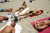 """Spain. Ibiza in the Balearic islands. Ibiza. Beach """" Den Bossa"""". Tourists (young men) take a rest and sunbathe on the sandy beach. © 1999 Didier Ruef"""