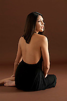 Young Hispanic woman seated, looking sideways
